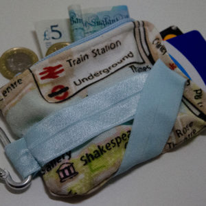 A minimalist travel wallet decorated with an oyster card and british pounds.