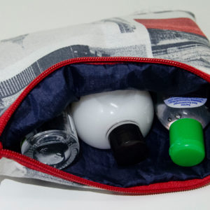 The pouch has a bright red zipper, blue fabric inside and is depicted with some santiser and gels.