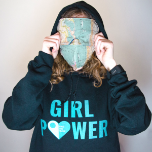 A person in a girl power Girls Who Travel hoodie with a world map face mask by Handmade by Martine and a world map blackout sleeping mask by Practicute.